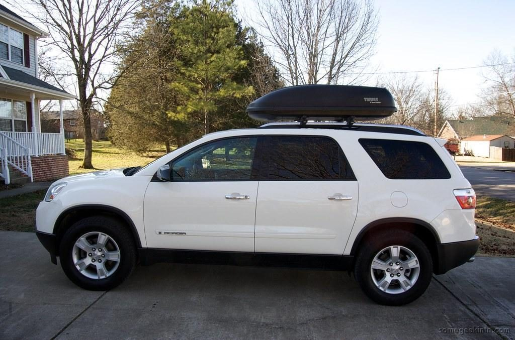 A white SUV with the cargo roof box